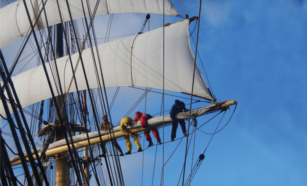 Hands aloft, stowing the 179-foot barque's mainsail.