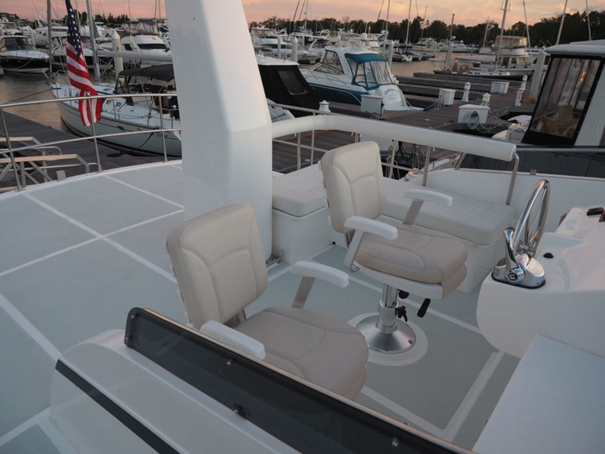 The flybridge has two chairs and companion seating to port. Add an optional powered crane and take advantage of room for dinghy stowage abaft the helm area.