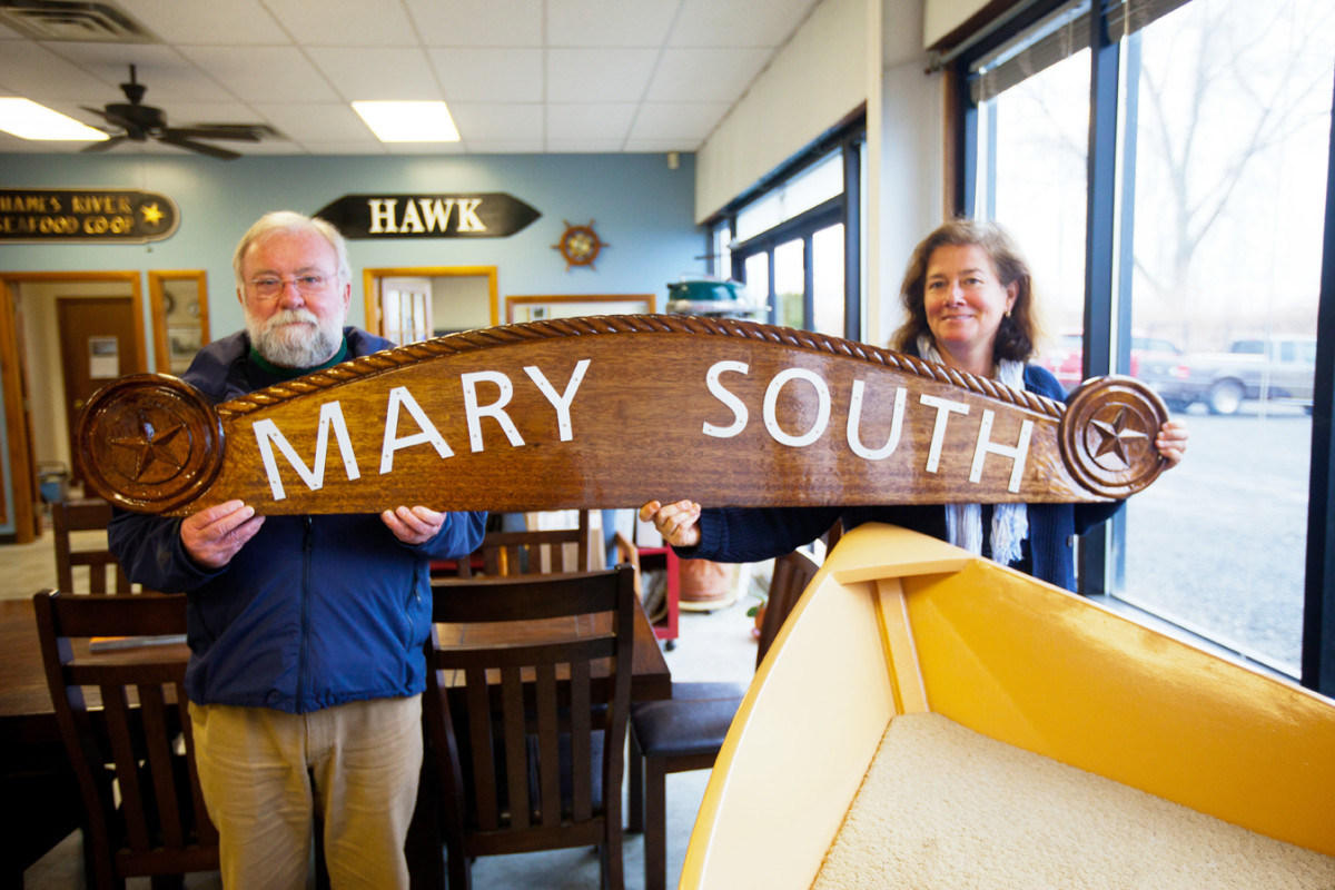 Bill Costigan and Soundings editor-in-chief Mary South hold the new nameboard for South's old boat.