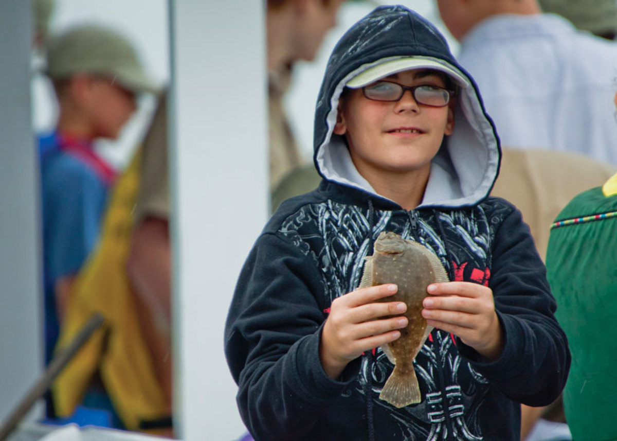 A young fisherman holds a small flounder, a fish that  may expand its habitat on the east coast as Atlantic currents slow down.