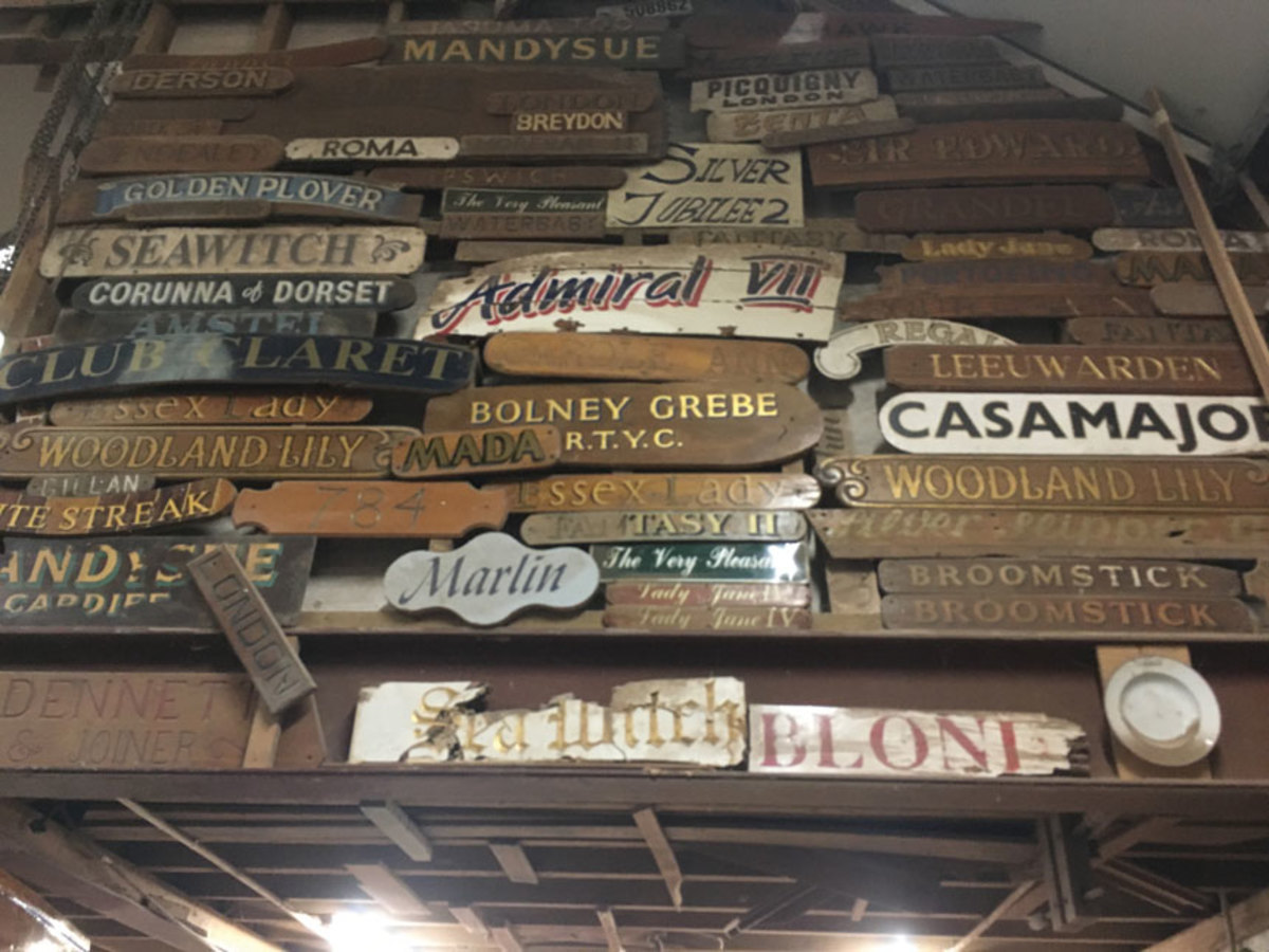 This collection of nameboards attests to the vessels that have passed through the Dennett's yard. Above, a brass plaque speaks to a boat's historic role.