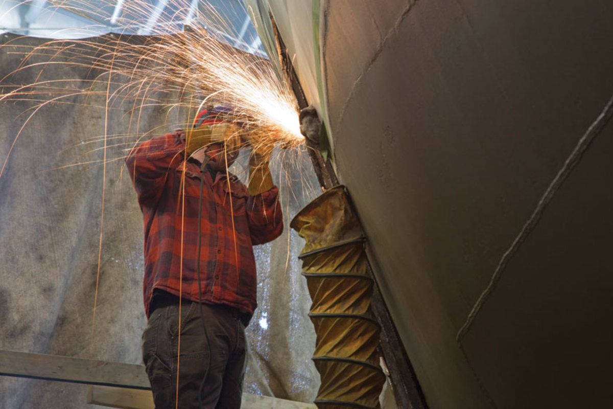 A welder at Front Street Shipyard works on the steel hull of the 80-foot Sindbad.