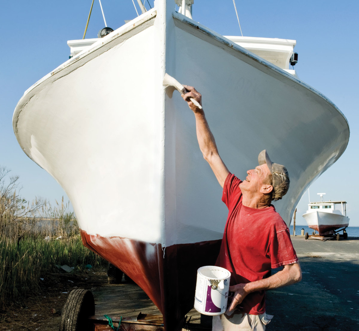 Mark Holitick paints Workaholic before the start of crabbing season.