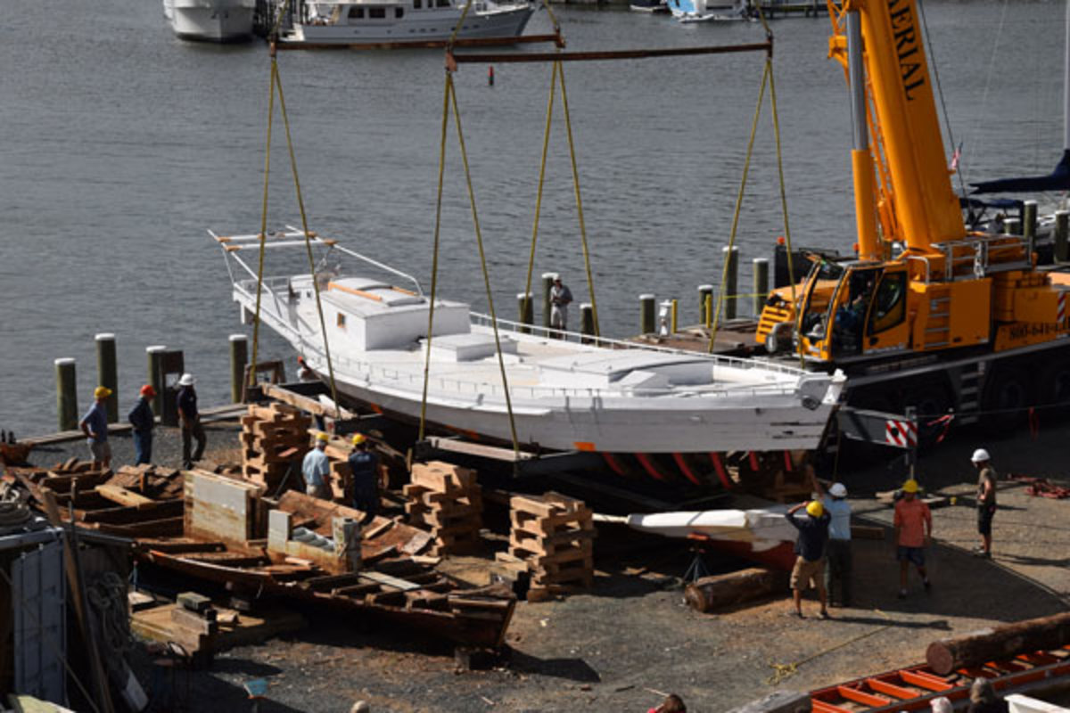 Chesapeake Bay Maritime Museum shipwrights crane Edna E. Lockwood's topsides and decks over her new log bottom.