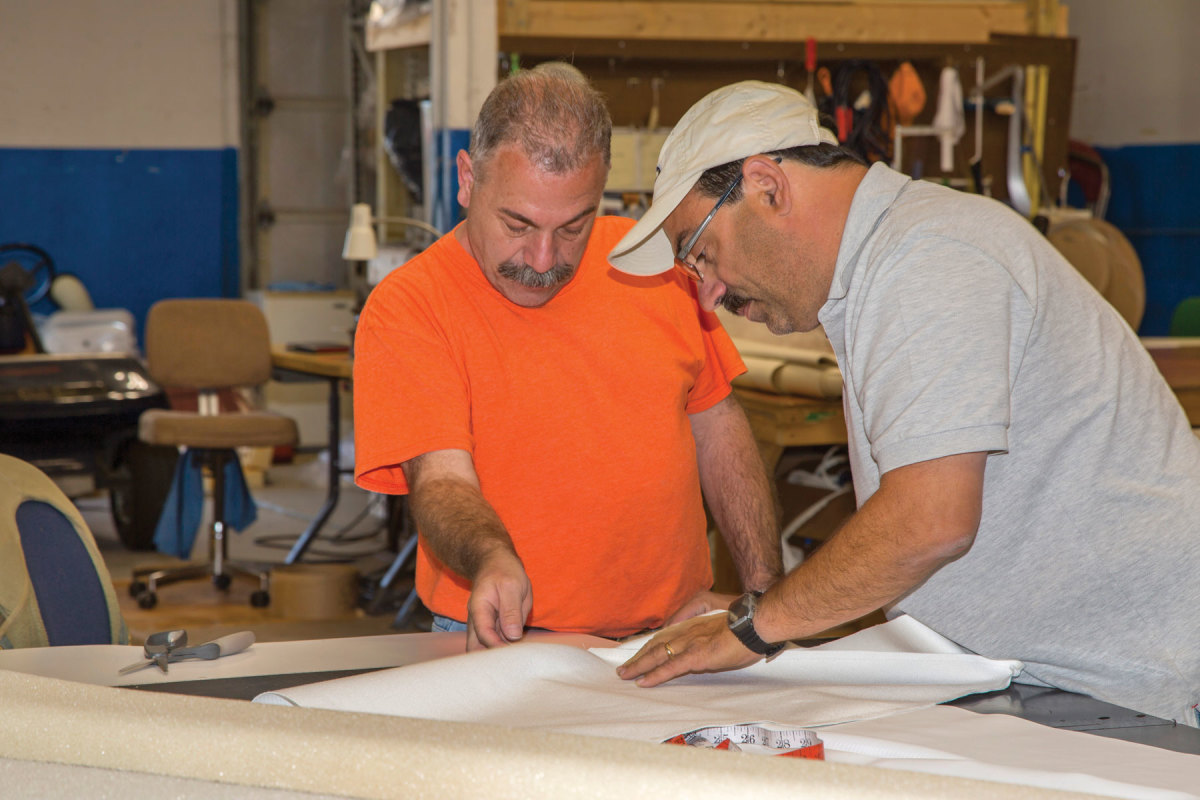 Upholstery shop manager Oscar DeLemos (right) confers with a craftsman.