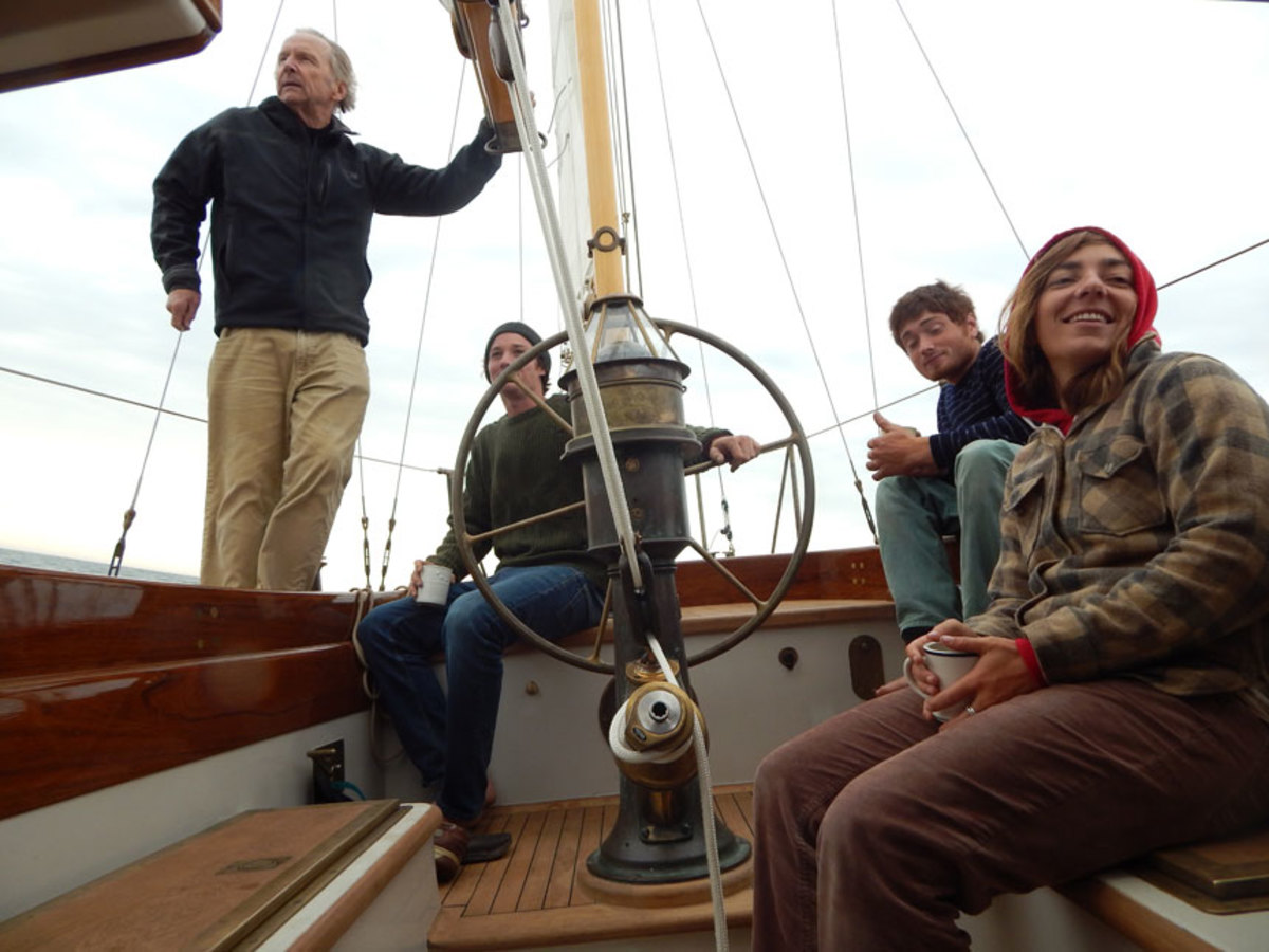 Owner Pat Ilderton enjoys an early morning on Vineyard Sound as shipwright-turned-captain Alex Goldhill and crew Zoli Clarke and Emma Thomson set Mah Jong on course for the WoodenBoat show in Mystic, Connecticut.