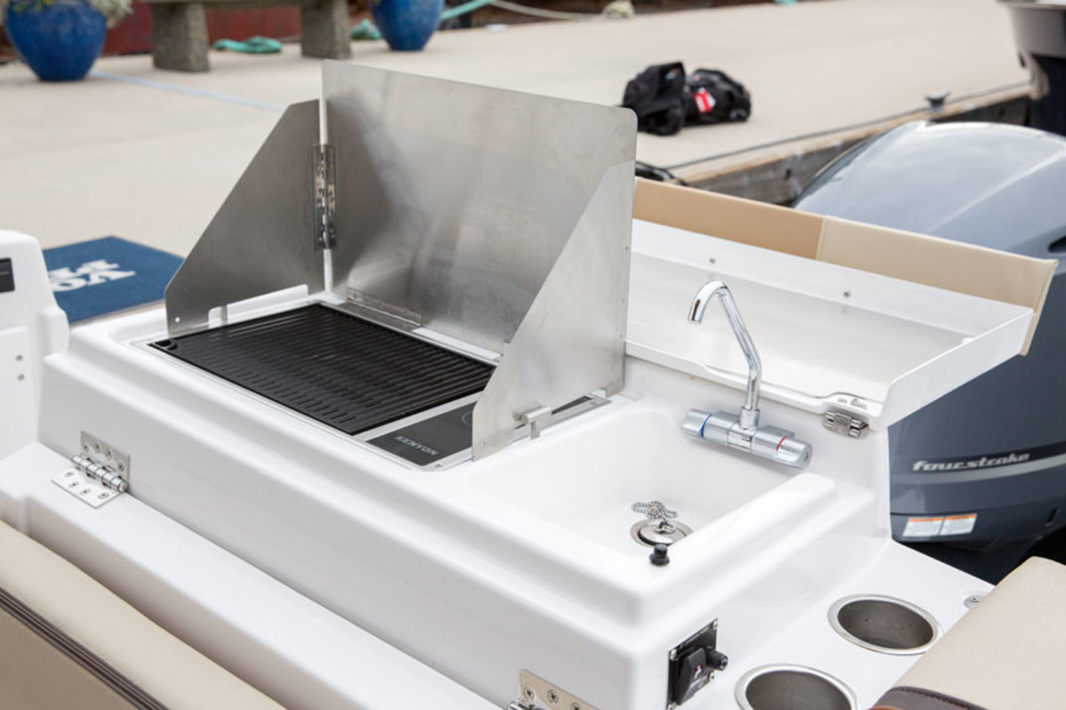 The transom features an electric grill and a sink with a freshwater mixer. The stowable grill lifts out to reveal a live well beneath it.