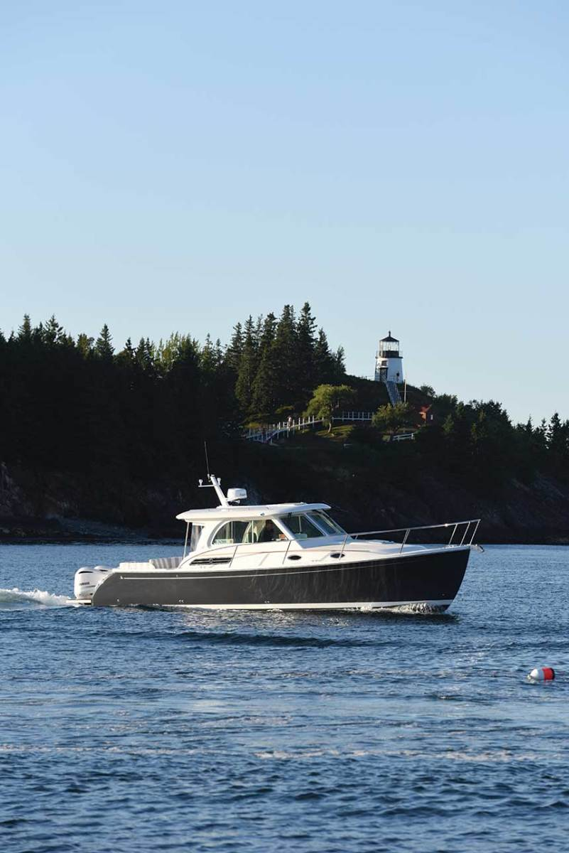 A Back Cove 34O with twin outboards cruises past the Owl Head Lighthouse.