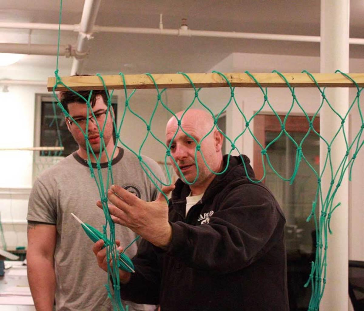 Joe Sanfilippo (right) teaches the critical skill of net-mending.