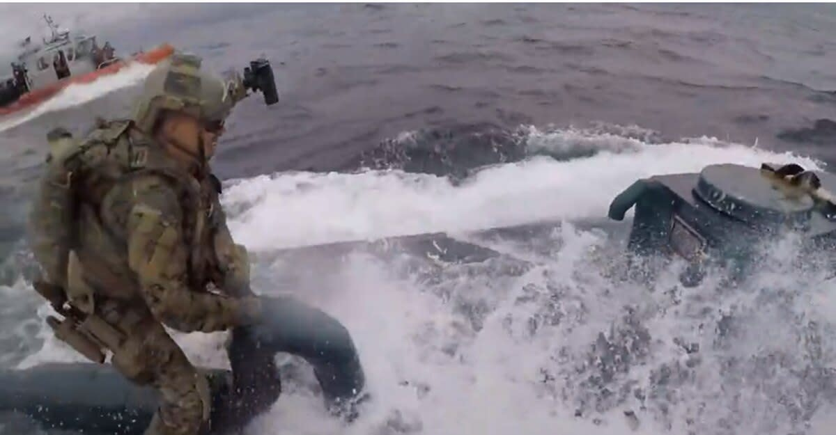 A Coast Guardsman hopped onto the back of a suspected drug-smuggling semi-submersible on the open ocean.