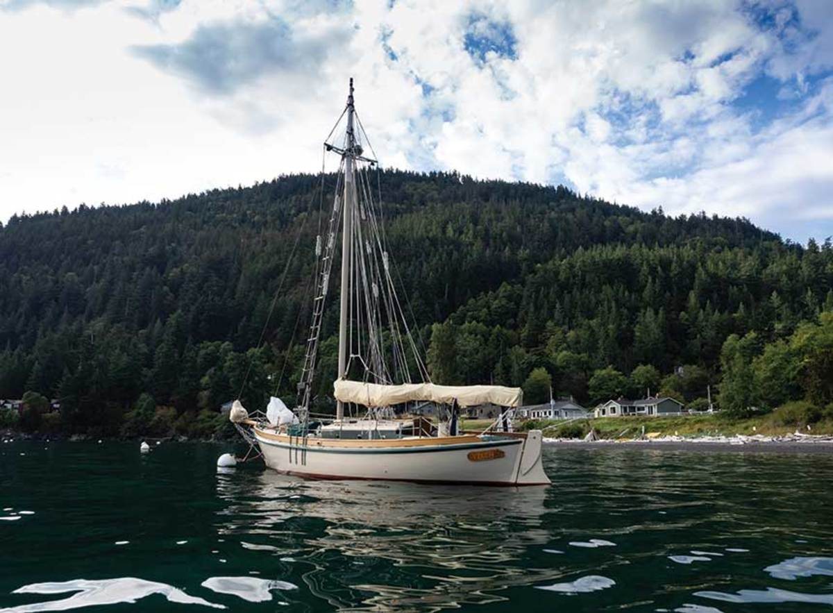Vixen, at anchor, is a  wooden gaff cutter designed by Atkin and Co. in the early 1950s; Les and Libby Schnick owned the boat before selling her to Halabisky in 2002.