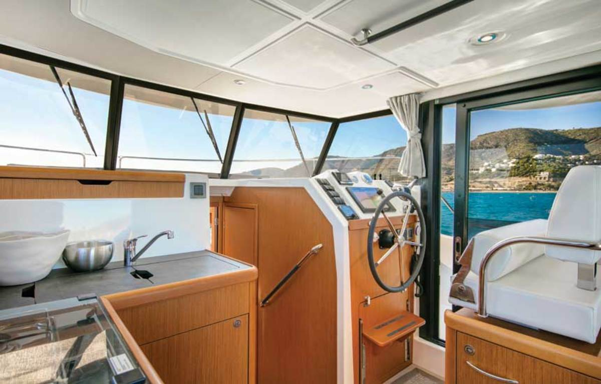 A sliding door at the helm provides side deck access.