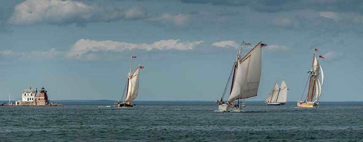 Schooners take laps after crossing the finish line at the Rockland Lighthouse.