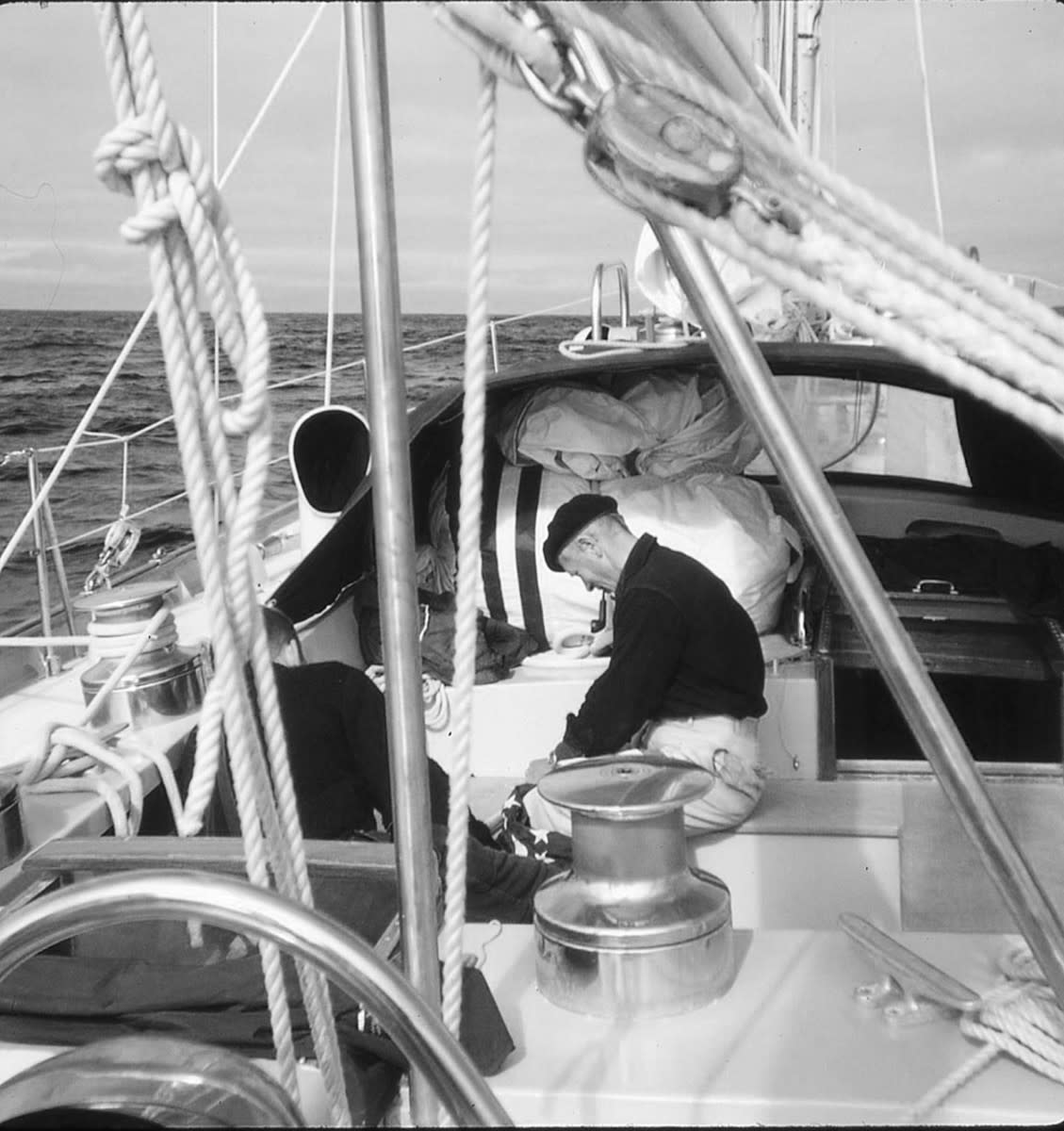 In the cockpit, a crewmember confers with the helmsman about the average course steered during his watch, and contemplates a course change.