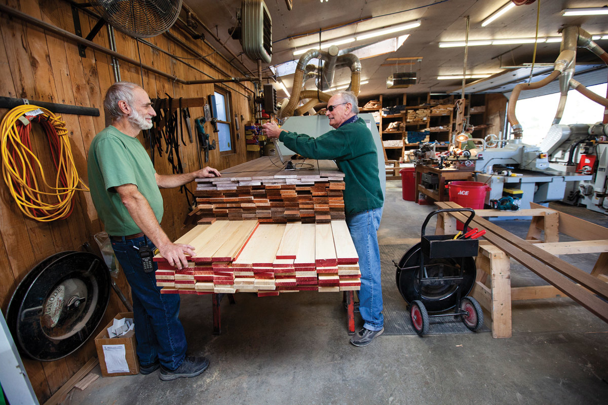 Simon and Dave Radoulovitch chat over a stack of cedar and walnut destined for Chesapeake Light Craft.