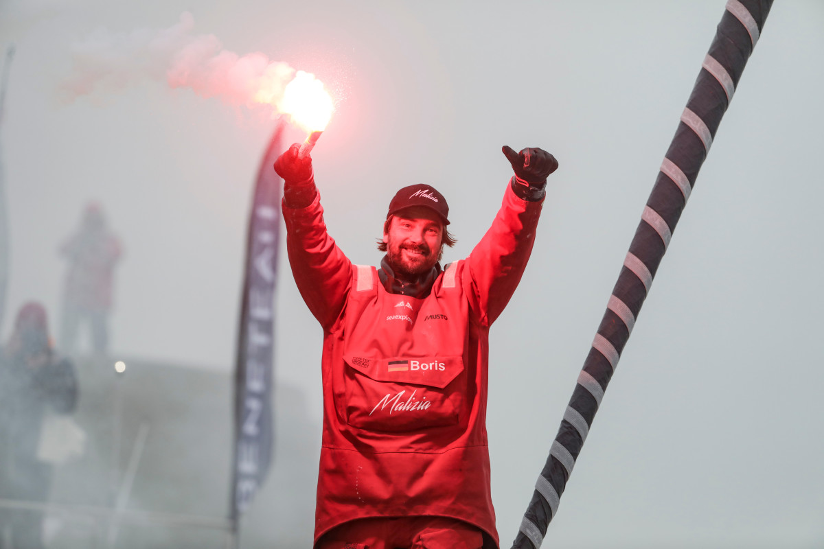 Despite a late collision that cost him a podium finish, Boris Herrmann celebrates at the finish with a smile and a flare.