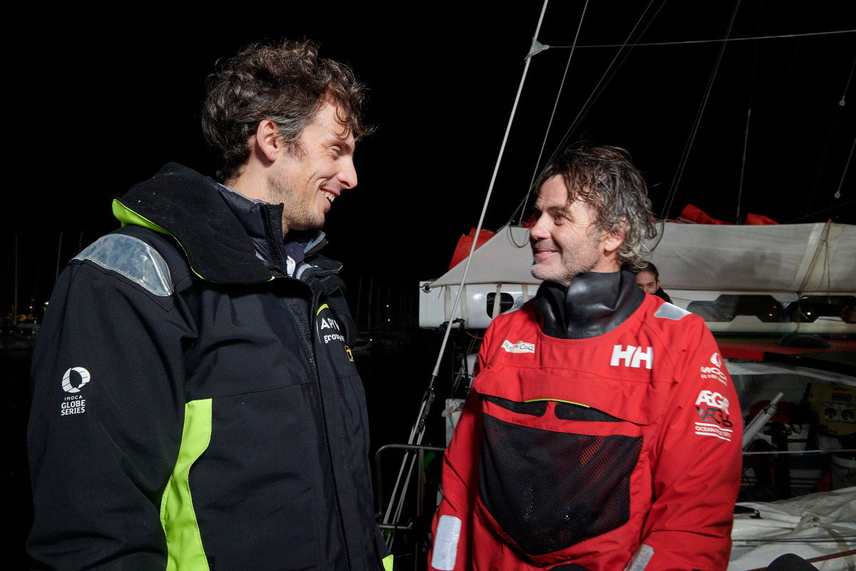 Charlie Dalin (left), who first crossed the finish line, greets Yannick Bestaven, the overall winner who was allotted extra time for his search and rescue efforts in the Southern Ocean.