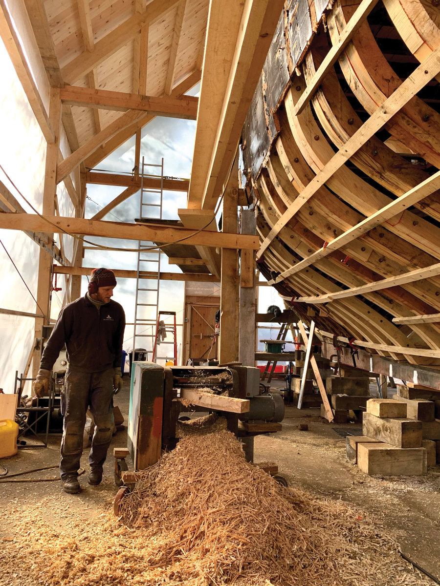 Inside the timber frame shed, shipwright Simon Larsen uses the planer to bring a futtock down to size.