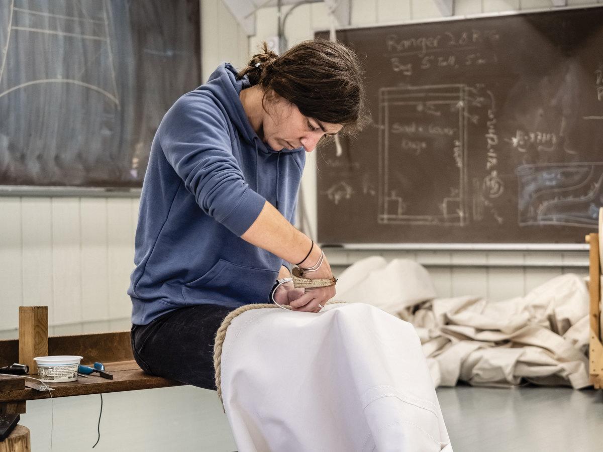 Emma Gunn sews a twine grommet.
