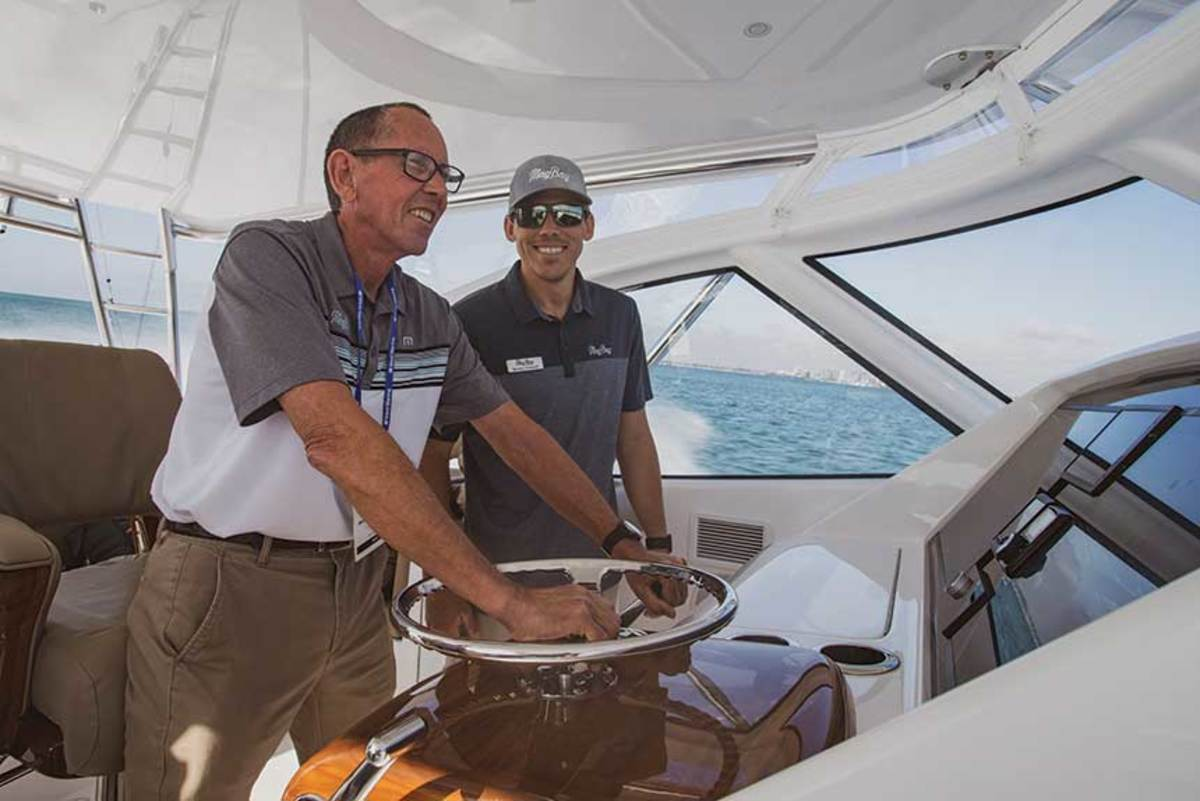 Mike Howarth puts down the hammer on the Mag Bay 42, and a smile on sonBarrett's face.