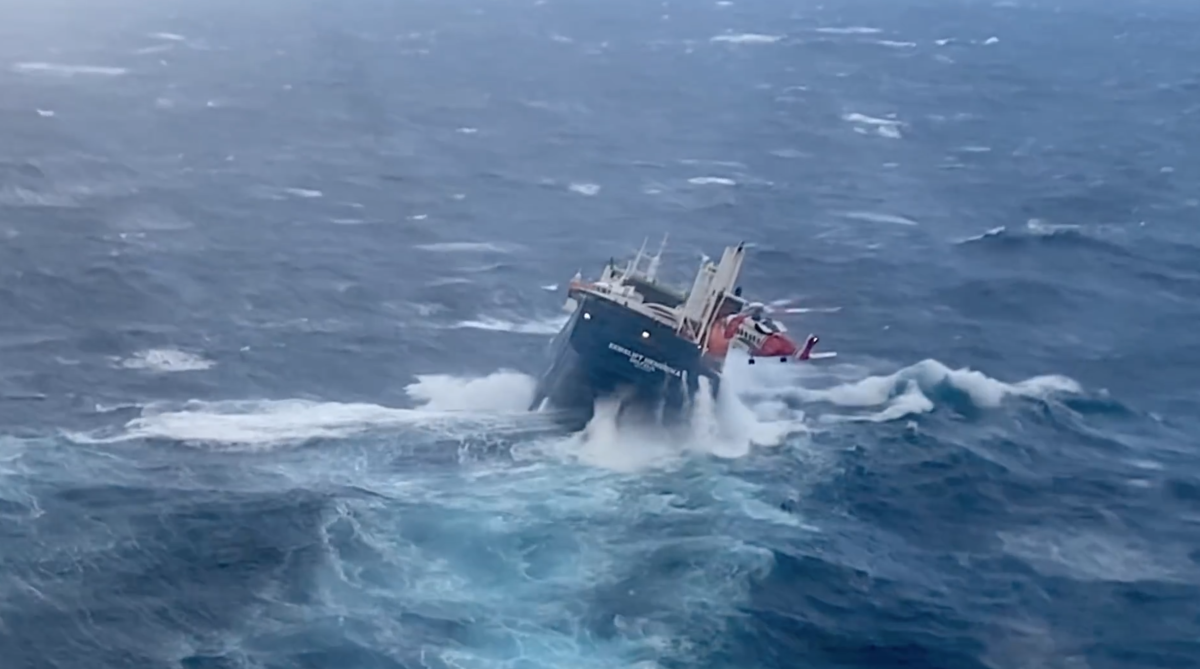 The transporter vessel drops its bow into a deep trough, exposing its running gear.