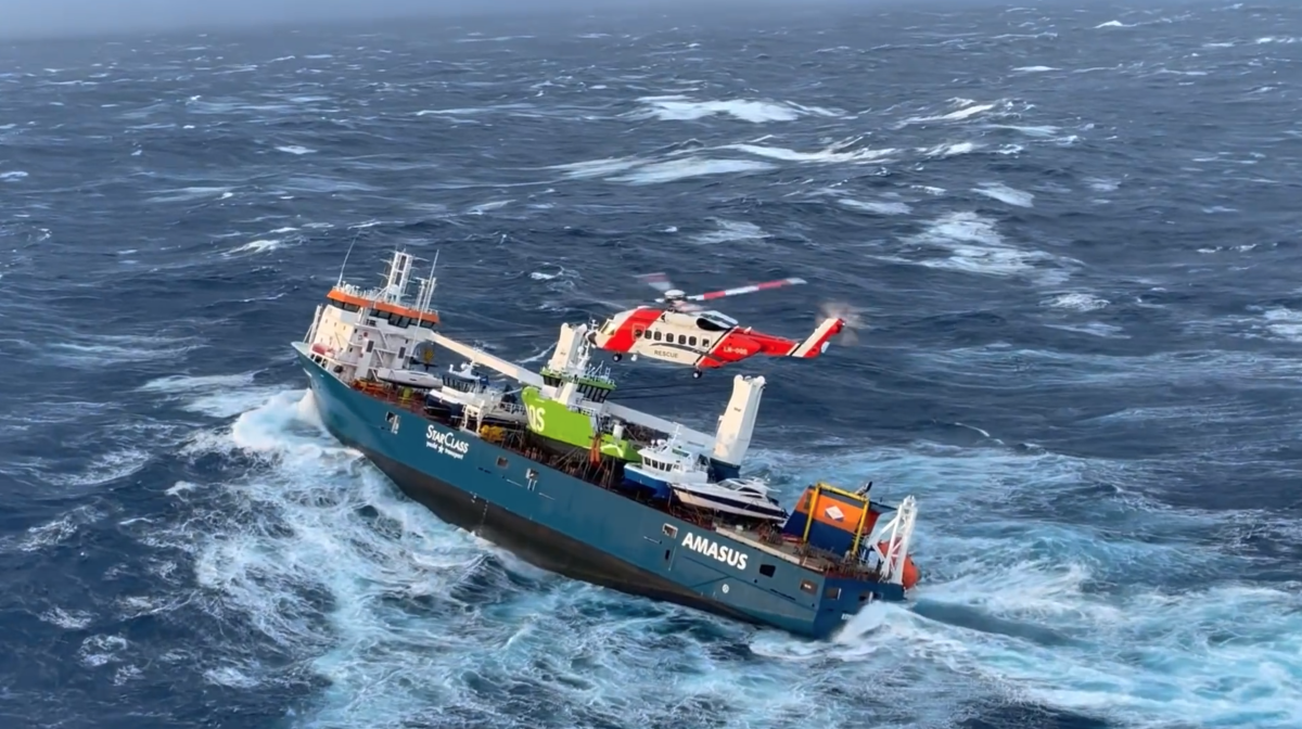 A Norwegian rescue helicopter moves in to retrieve crew from the listing ship