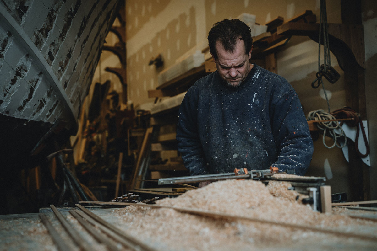 Top: A craftsman mills strakes for the hull layup.