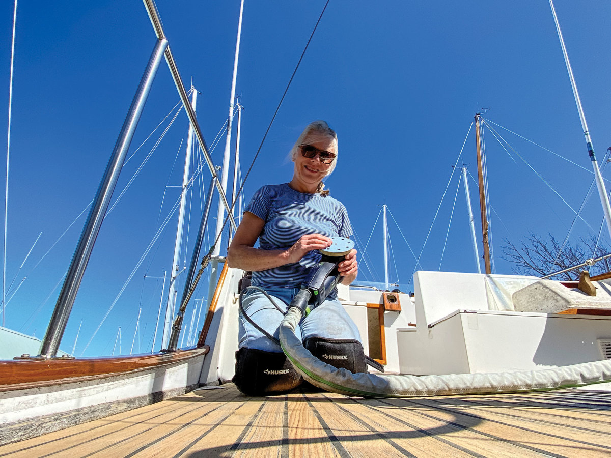 Tenley van der Wal sanded the upper deck on Snow Goose to level off the old caulking and bring new life to the teak.