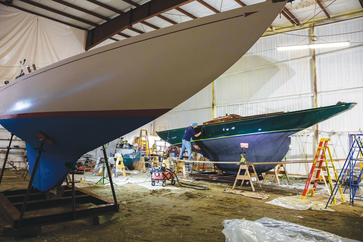 Dave Partridge repaints an IOD hull at the John Williams Boat Company.